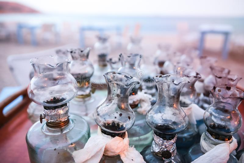 Old Oil Glass Lamps with DIY fixes gathered on Table on Greek Beach at Sunset royalty free stock photo