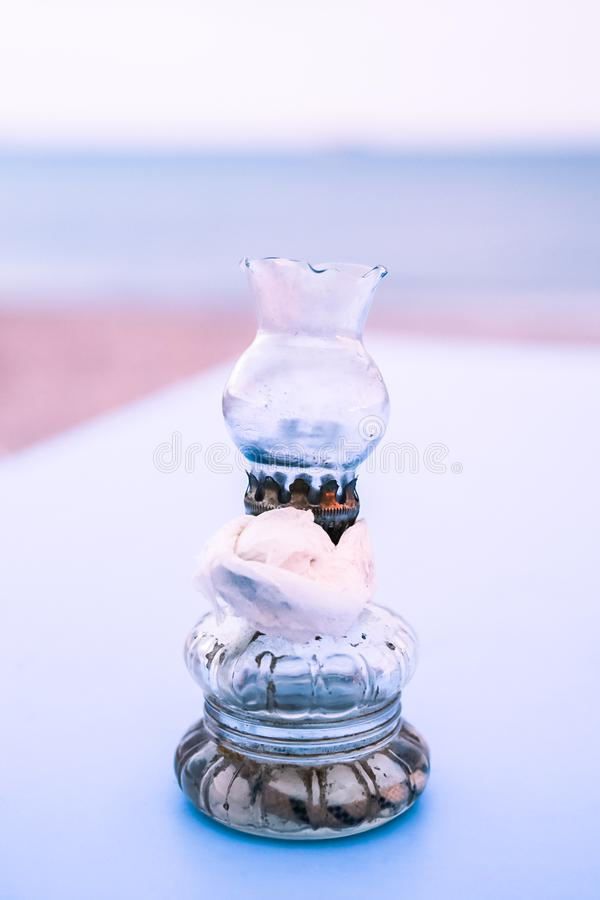 Old Oil Glass Lamps with Paper Napkin on Blue Table on Greek Beach at Sunset stock photography
