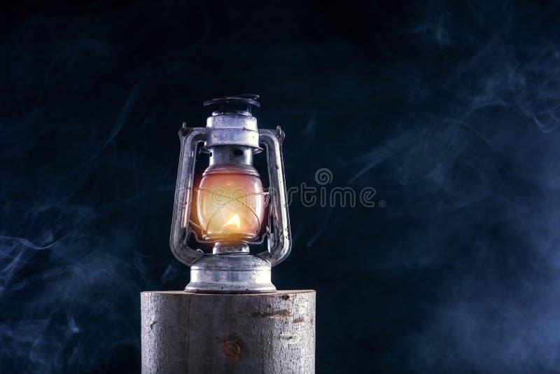 Old oil lantern burning at lumber log and foggy smoke dark night royalty free stock photography