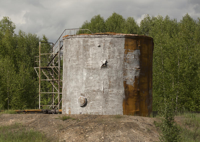 Old oil storage tank. On the forest background stock images
