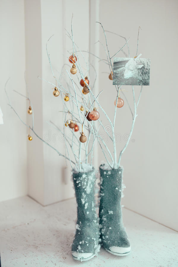 Old-old felt-boots. Snow-covered felt boots & tree branch decorated room royalty free stock photo