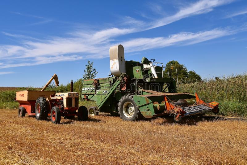 Old Oliver 431 combine and Case tractor. ROLLAG, MINNESOTA, September 1, 2018: An old Oliver 431 self propelled combine and Case tractor participate in field royalty free stock photos