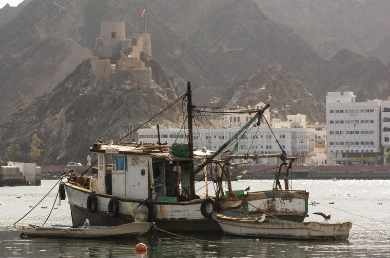 Old Omani fishing vessel in port with Muscat castle stock image