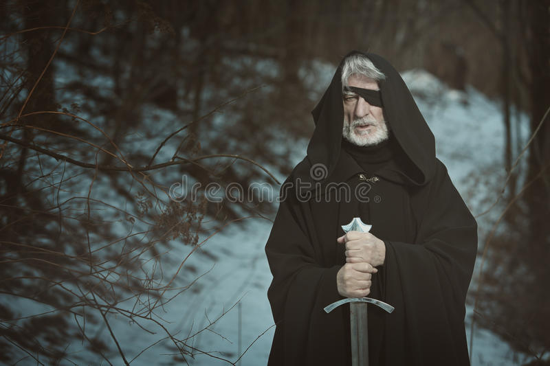 Old one eyed man with sword in dark forest stock photo