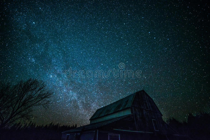 Old Ontario Barn and the night stars. An old ontario barn with gambrel roof on a rural farm is silhouetted in the night sky. The winter Milky way is brilliant royalty free stock photography