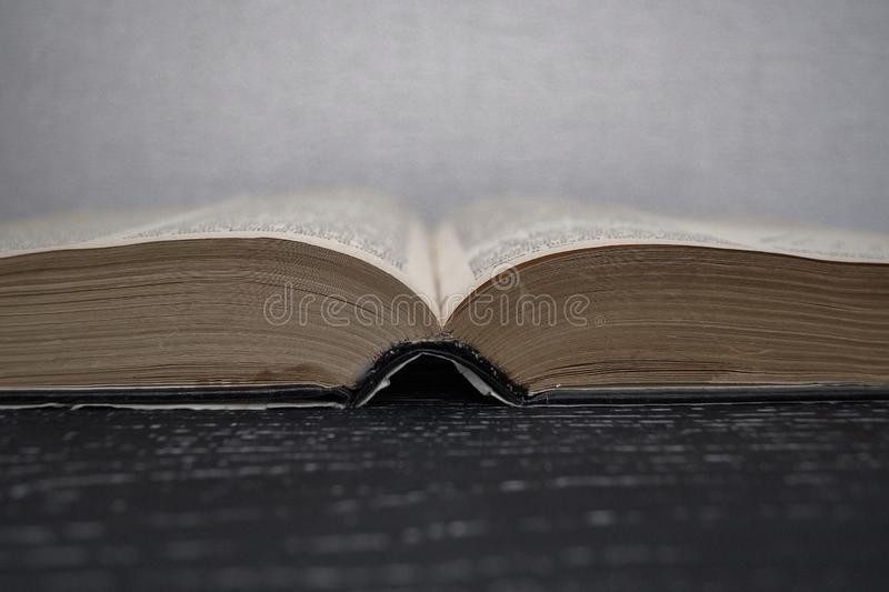 Book. An old open book lies on an old black wooden table stock photo