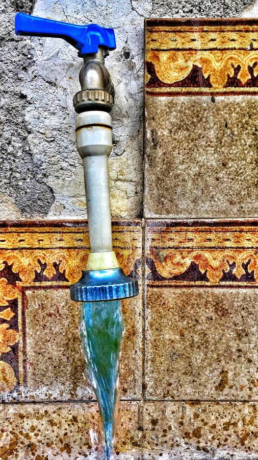 Old open faucet. Dramatic old grunge abstract open faucet with flowing blue water royalty free stock photography