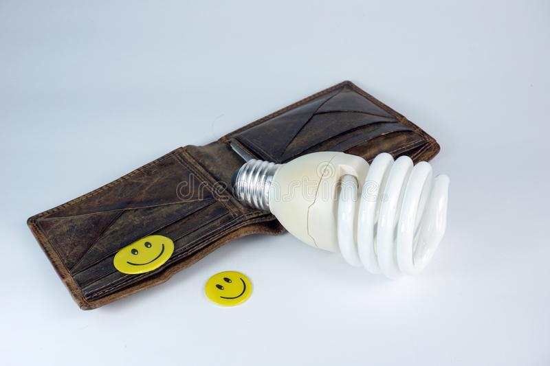 Old open Leather wallet with energy saving bulb happy smiley faces  on white background. Finance and savings stock photography