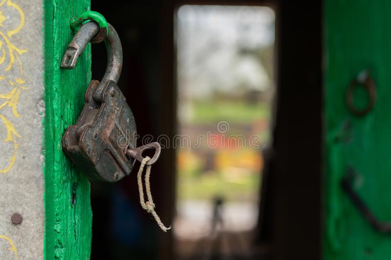 Old open lock with key on the door. Old scratched lock hanging on the green door. The key is inserted into the lock. Canon EOS 77D, f/3.2, ISO100, 1/320. Noon stock photos