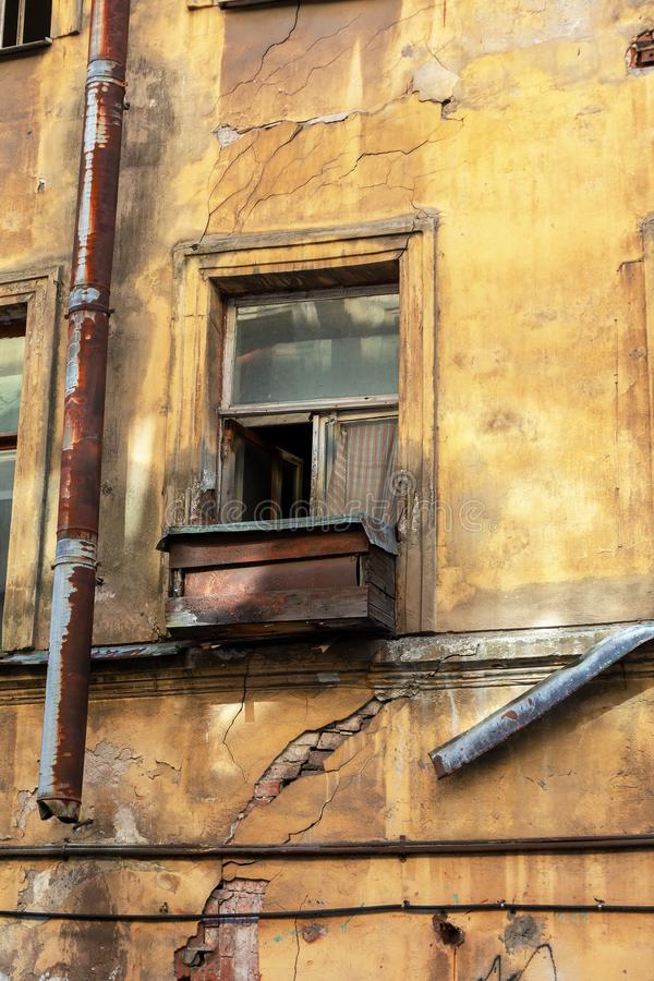 An old open window with a curtain and a wooden box on the windowsill in an abandoned apartment building. close up. royalty free stock photo