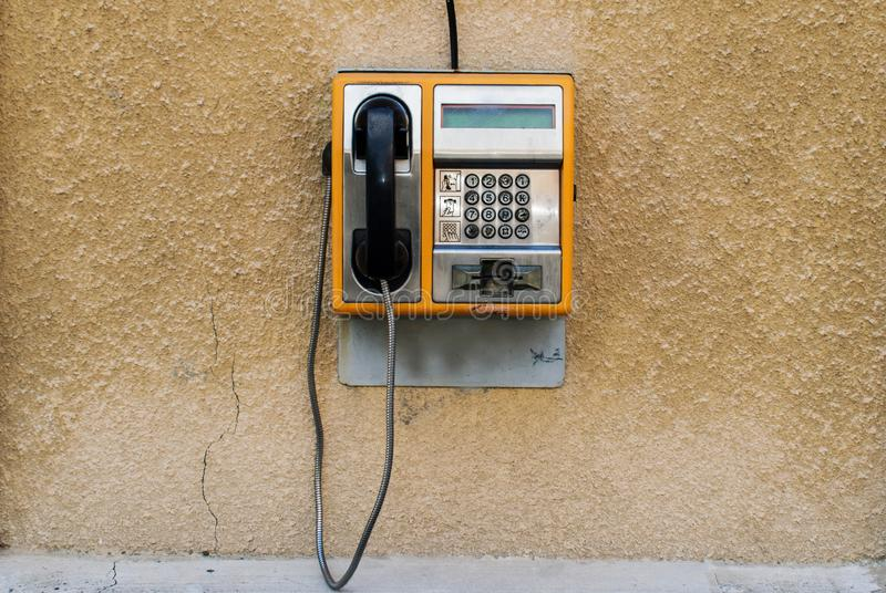An old orange phone with a card. Street phone on a wall. This phone was used in Europe in the 1990s royalty free stock photography