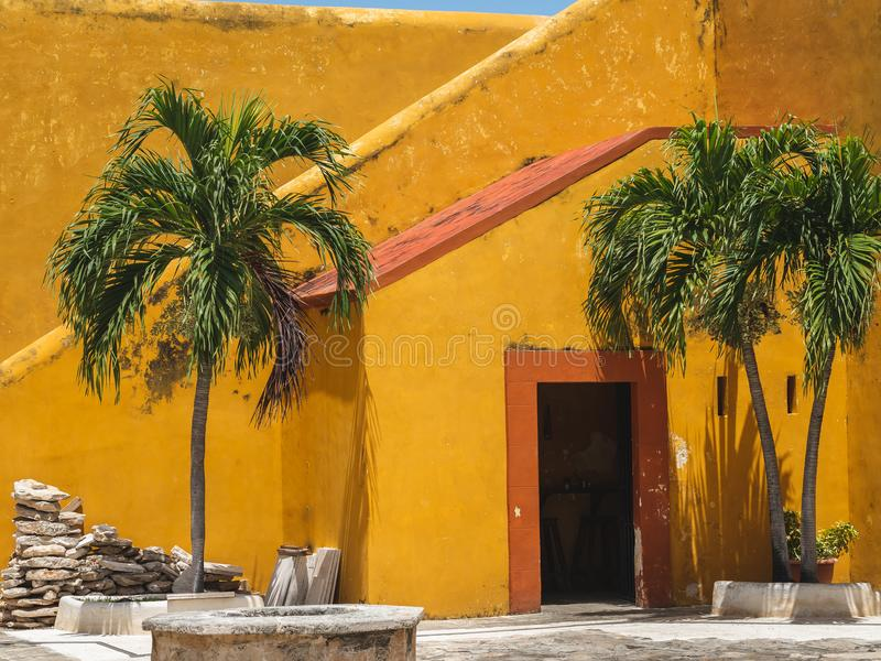 Old orange and yellow door and stairs of a Spanish-colonial style building in Mexico royalty free stock photography
