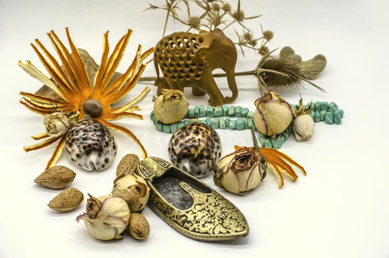 Old oriental souvenirs of wooden elephant, turquoise beads, brass slipper in the form of ashtrays, dry buds, thorns, shells on whi. Still life of old oriental stock photo