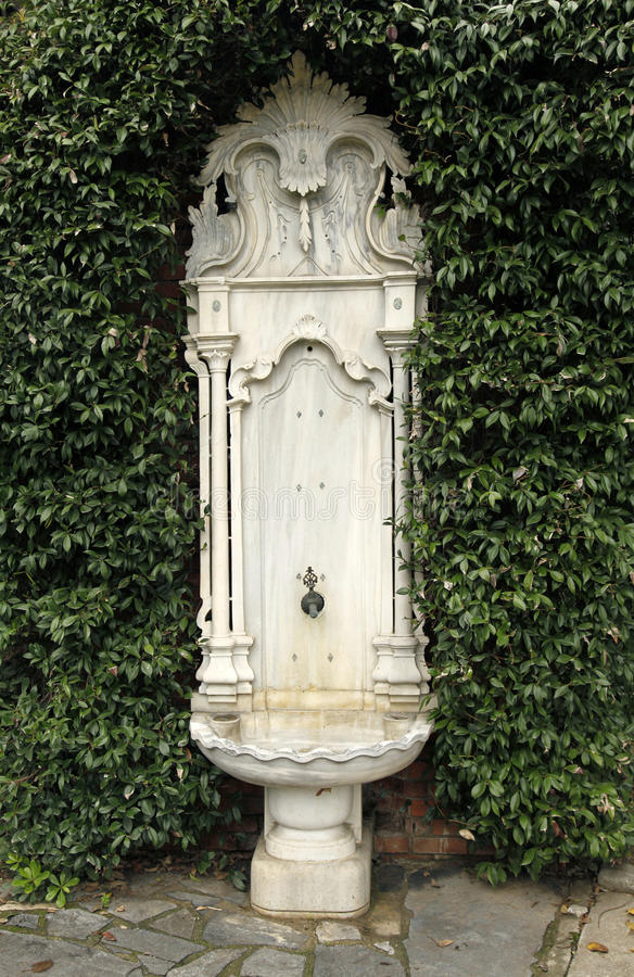 Old, ornate, embossed marble, ottoman fountain. In the forest surrounded with plants royalty free stock photos