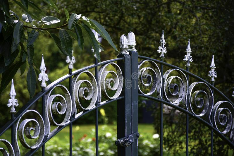 Old ornate metal gate door outdoors. Decorative cast iron wrought fence royalty free stock image