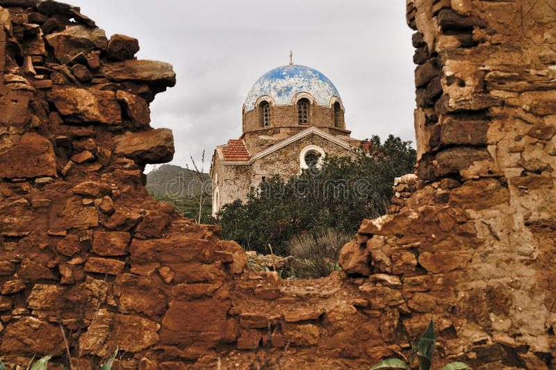 Old orthodox church and fallen wall. Old orthodox church framed by a fallen wall ruins under sky with clouds in Attica, Greece royalty free stock photo