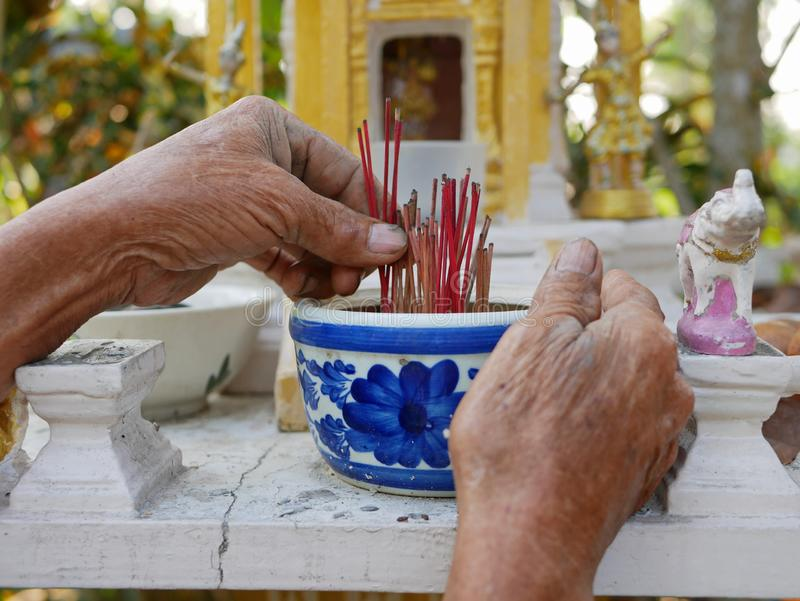 Old outdoor hard-working man`s hands removing burnt incense sticks in a pot on a spirit house royalty free stock photo