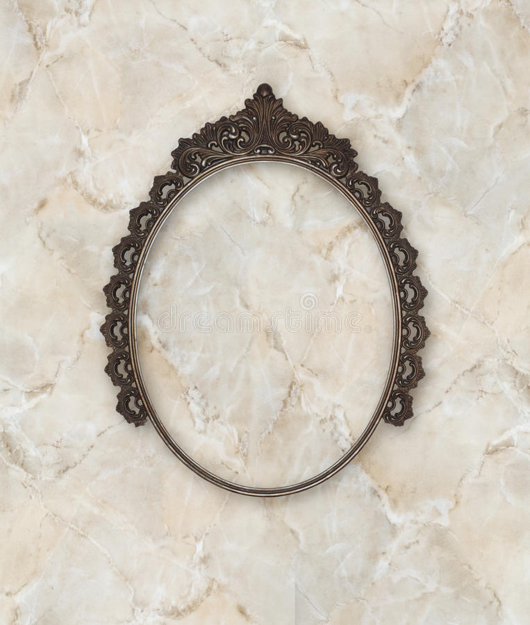 Old oval picture frame metal worked on marble background. Old oval picture frame metal worked on marble bathroom background royalty free stock images