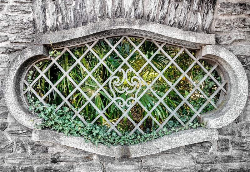Old oval window with iron bars. Old oval window with iron bars in stone wall stock photos