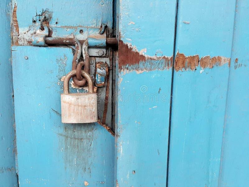 Old padlock and blue door stock photo