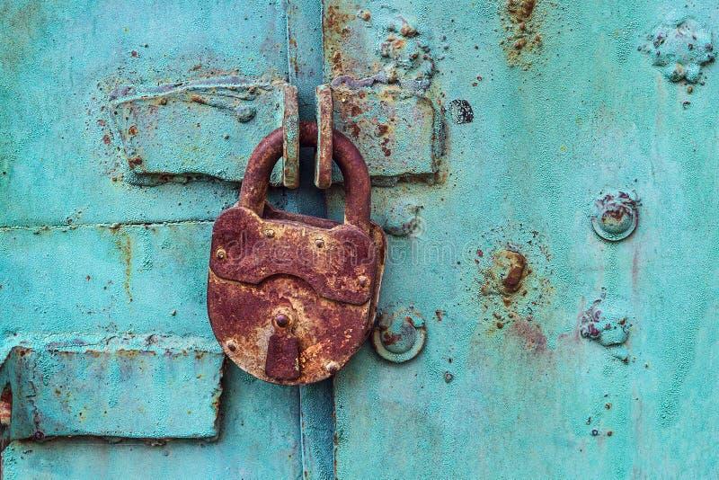 Old padlock on a blue door. Old rusty padlock on a blue iron door stock photos