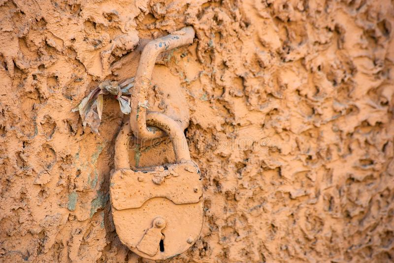 Old padlock on a metal bracket in a stone wall. Soft focus, retro, vintage, old-fashioned, weathered, closeup, secure, security, safety, steel, decay royalty free stock photos