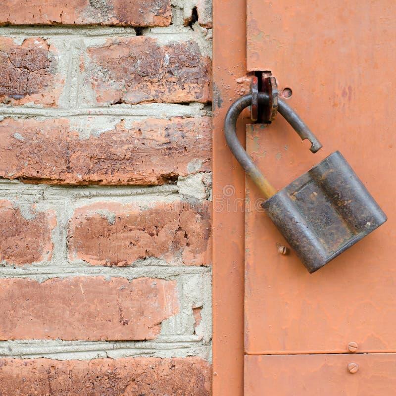 Old padlock on metal door. Red brick wall stock photography