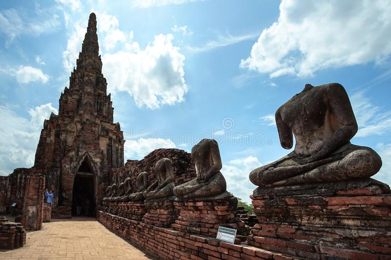 Old pagoda and ruined Buddha statue in Chaiwatthanaram temple. royalty free stock photos
