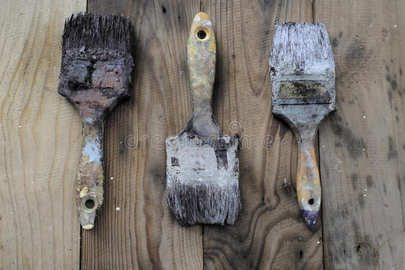 Old paint brush on wood stock photo