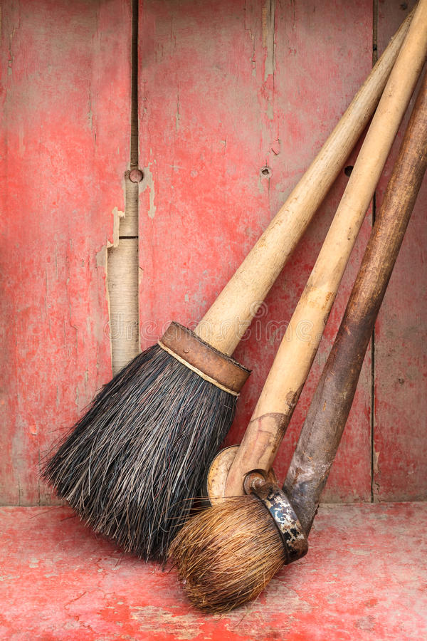 Old paint brushes against a red wooden background royalty free stock photo