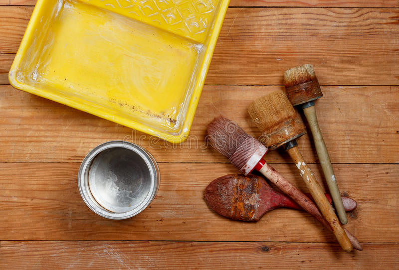 Old paint brushes, metal cans and plastic paint tray paint on wooden boards stock photography