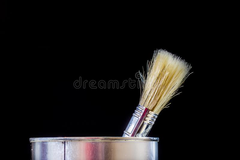 Old paintbrushes for paint, Cans of paint on wooden table. Paint stock image