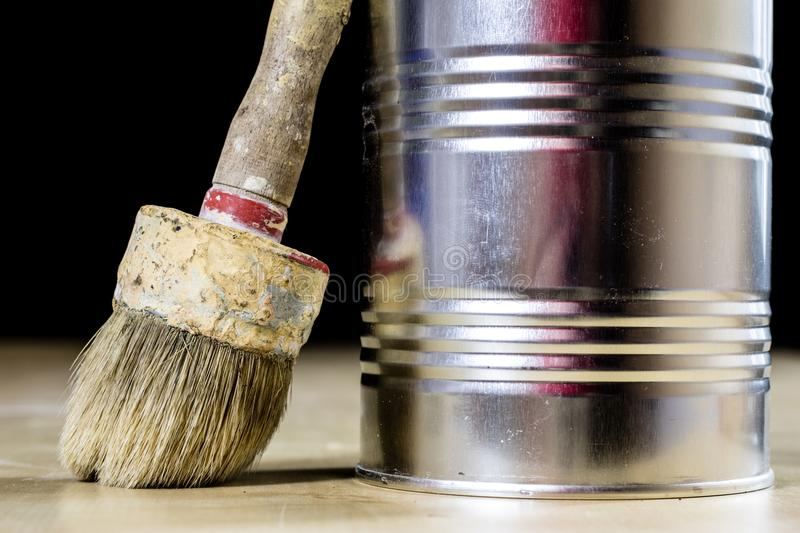 Old paintbrushes for paint, Cans of paint on wooden table. Paint royalty free stock image