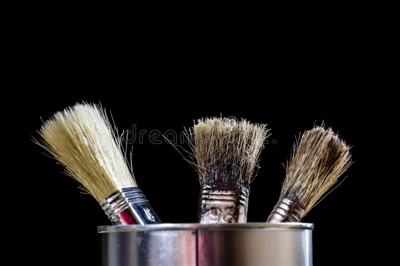 Old paintbrushes for paint, Cans of paint on wooden table. Paint royalty free stock photography