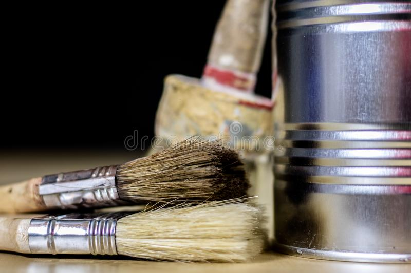 Old paintbrushes for paint, Cans of paint on wooden table. Paint royalty free stock images