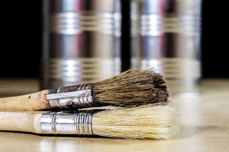 Old paintbrushes for paint, Cans of paint on wooden table. Paint royalty free stock photos