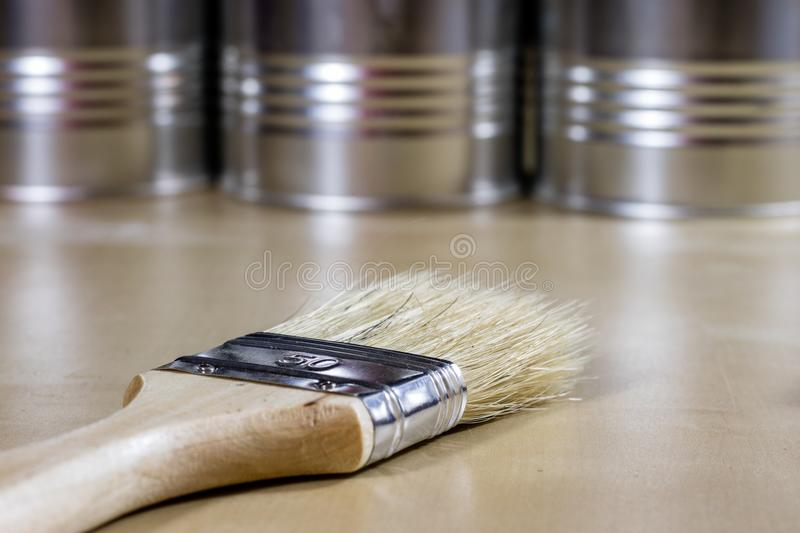 Old paintbrushes for paint, Cans of paint on wooden table. Paint royalty free stock photo