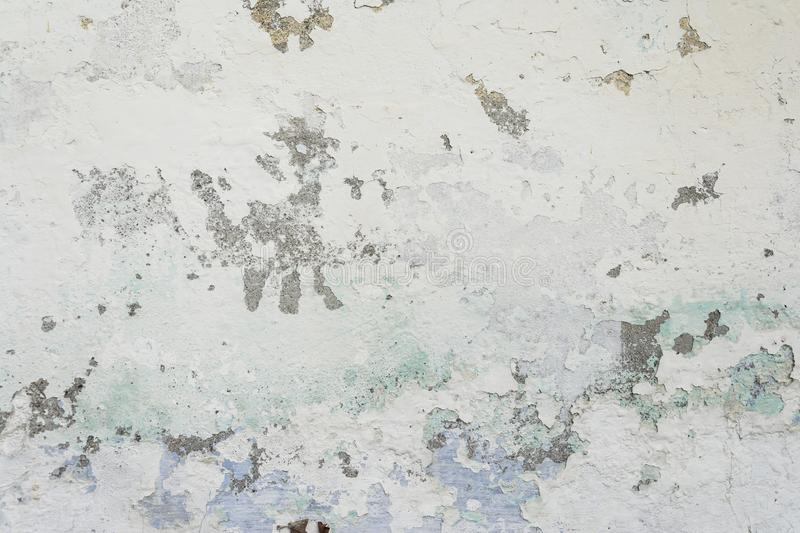 Old painted cement wall with all the cracks and peeling layers. Texture background royalty free stock photo