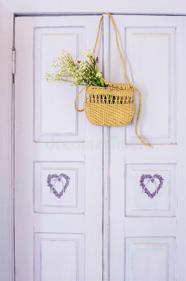 Old painted lilac doors and a wicker bag on the door with a bouquet of wild flowers. Vintage retro photo. The atmosphere of recrea stock photography
