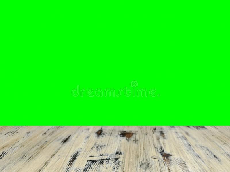 Old painted washed oak wood table on the blurry chroma key green screen wall background, wooden table royalty free stock photo