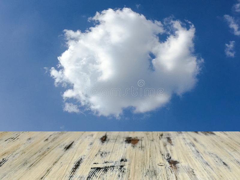 Old painted washed oak wooden table on the blue sky clouds background, wood table royalty free stock photos