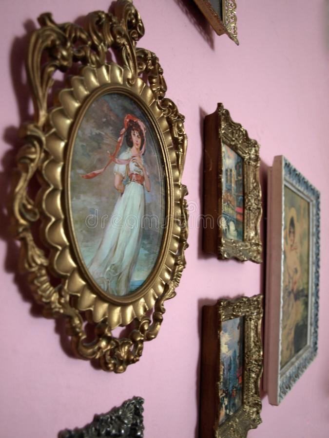 Old Paintings in Gold Frames Hanging on a Pink Wall stock images