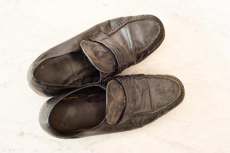 Old pair of Mens black dress shoes that are worn out, very dusty and dirty and falling apart.  They need polish and repair stock photography