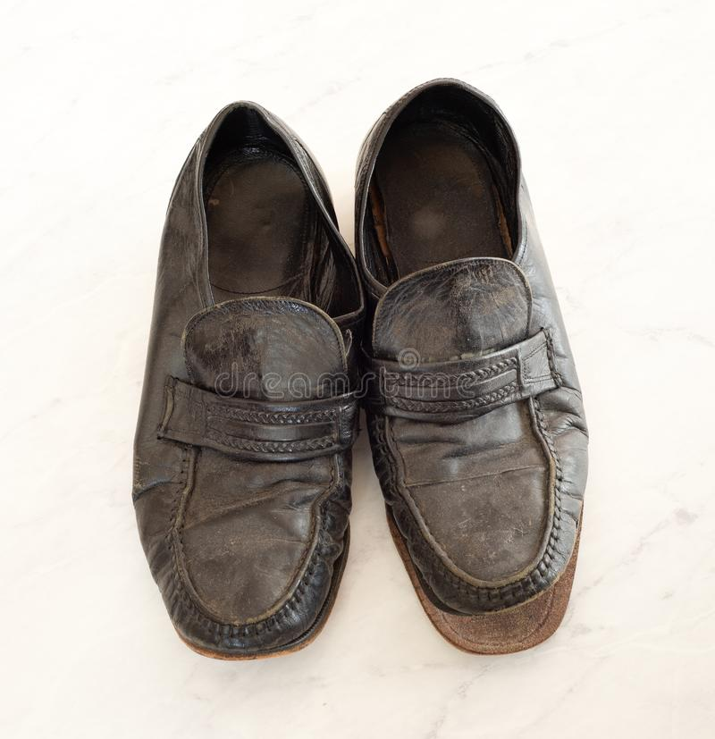 Old pair of Mens leather black dress shoes that are worn out, very dusty and dirty and falling apart.  They need polish and repair royalty free stock image