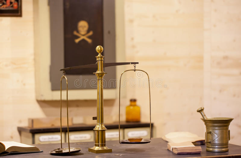 Old pair of scales and mortar in a pharmacy. An old mounted brass pair of scales and a mortar in a very old pharmacy stock image