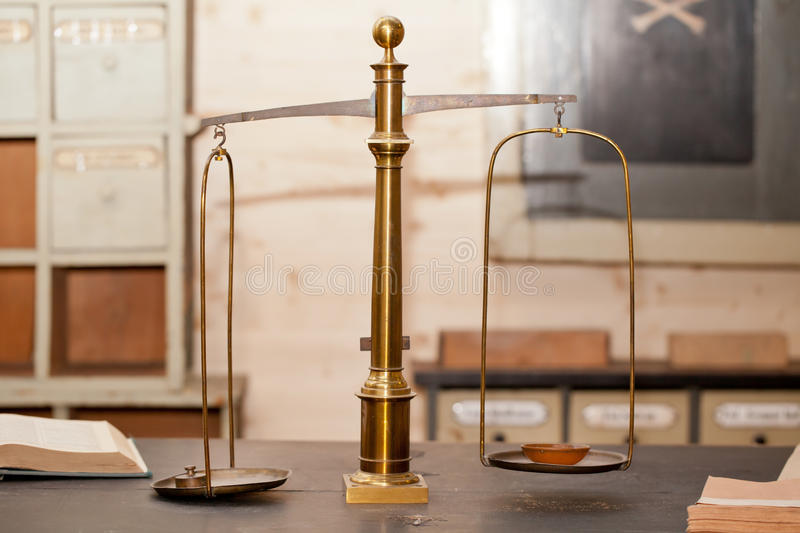 Old pair of scales in a pharmacy. An old mounted brass pair of scales in a very old pharmacy royalty free stock images
