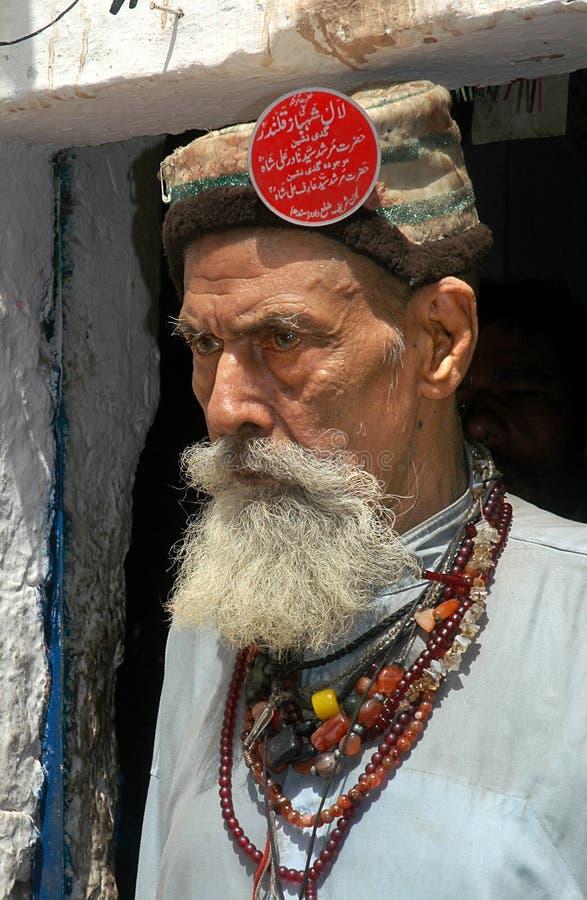 Old Pakistani man with a black beard smoking a cigarette in Peshawar, Pakistan. Old Pakistani man with a hat and red badge in Peshawar, Pakistan. Pakistani man stock photo