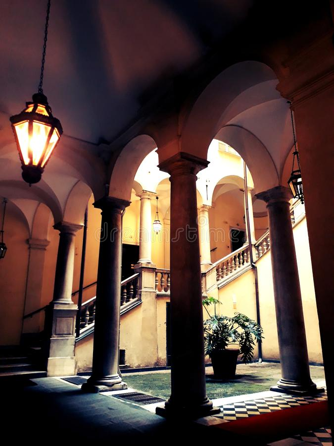Old palace`s hall in Genoa. An old palace in Genoa`s center, with its elegant architecture inspires a past not so far. A little garden closed by columns near the stock photo