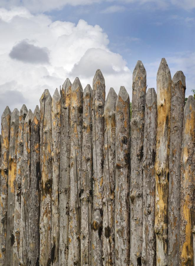Old palisade of sharpened logs against the sky. Old paling of sharpened logs on sky background royalty free stock image