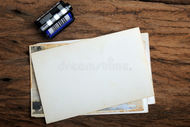 Old paper photo frame with camera film on wood background stock images
